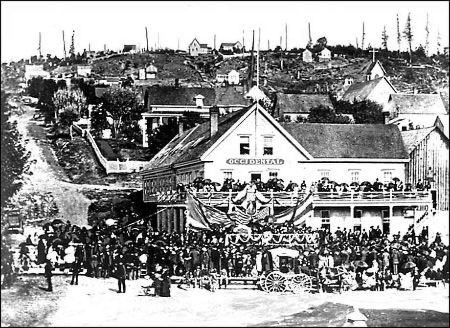 Gathering at the Occidental Hotel, 1881: Citizens collect in the square in front of the Occidental Hotel at the corner of Front Street, later renamed First Avenue, and Yesler Way in September 1881 to attend memorial services for assassinated President James Garfield. The section of the city seen behind the hotel was known as Profanity Hill. Photo: Seattle Post-Intelligencer