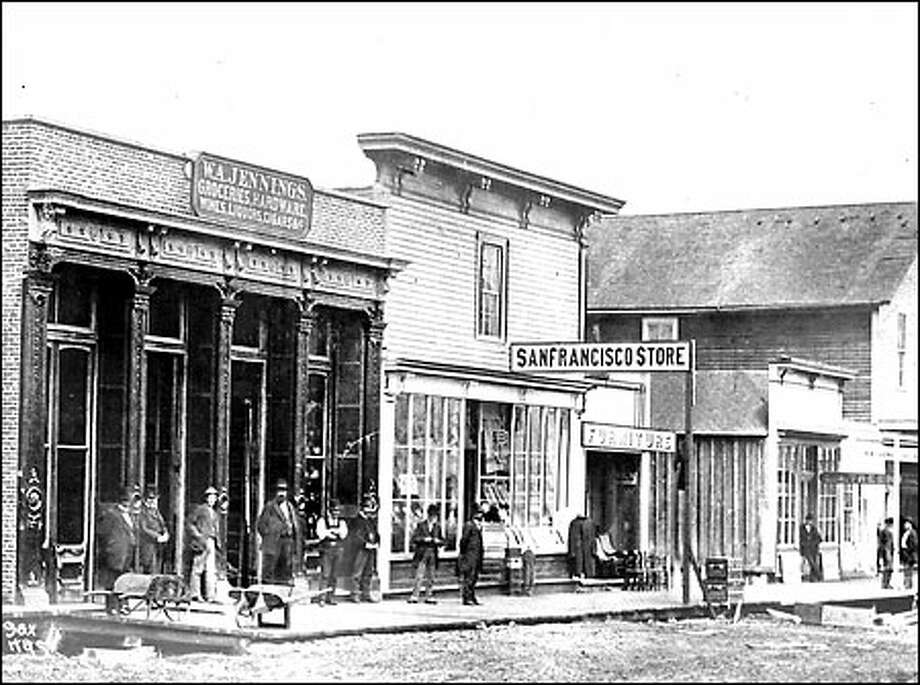 Merchant's row, 1877: A row of storefronts sits along Commercial Street (later renamed First Avenue South) between Washington and Main streets in 1877. The San Francisco Store was the forerunner of the Seattle department store MacDougall and Southwick. Photo: Seattle Post-Intelligencer