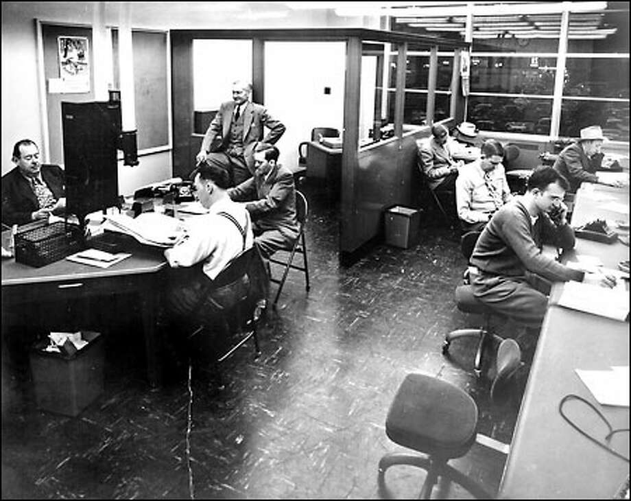 Legendary P-I sports editor Royal Brougham, standing in upper left, supervises sports writers in the new P-I building, 1948. Photo: Seattle Post-Intelligencer