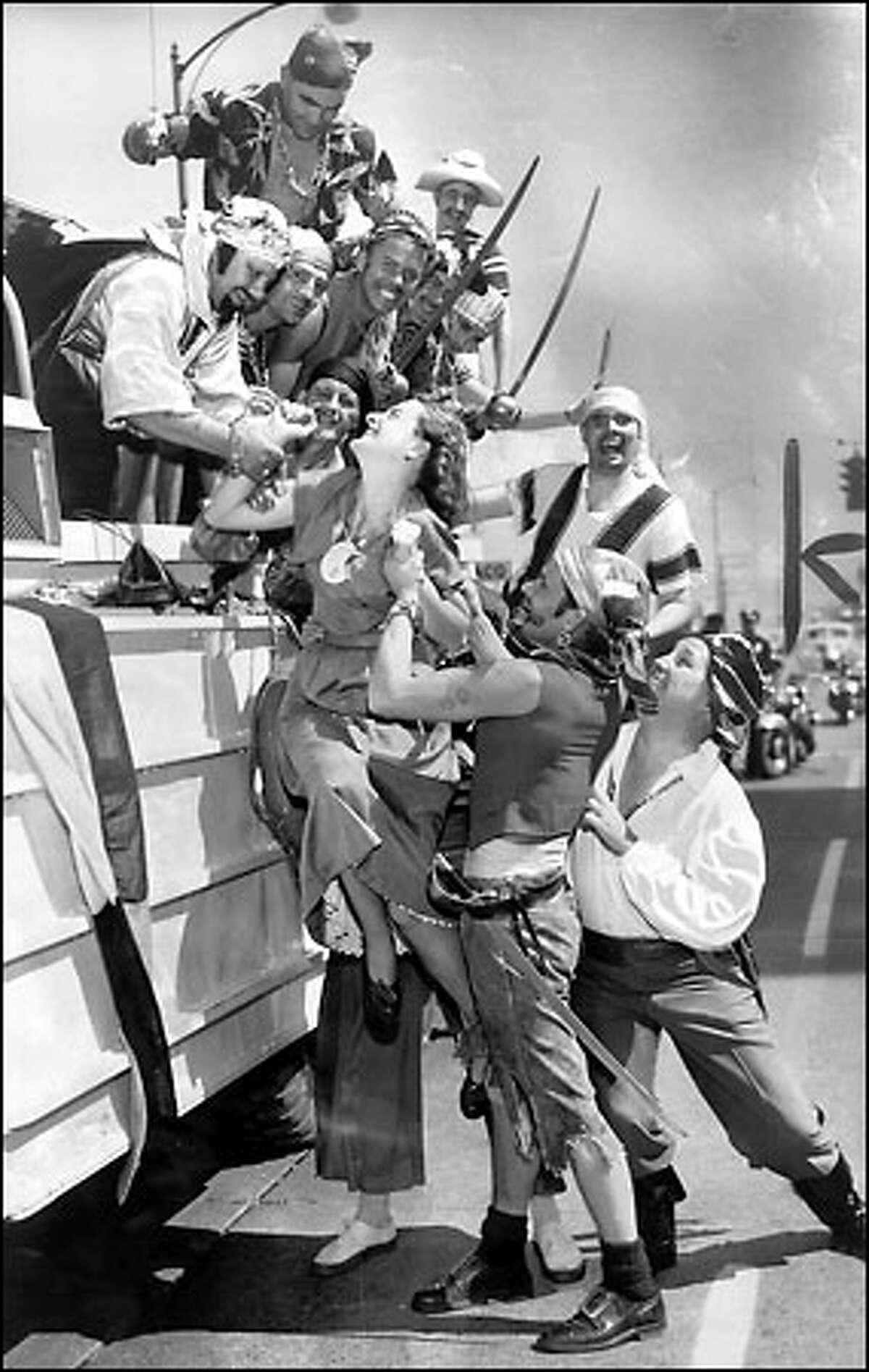 Abduction by Seafair Pirates, 1951: Janet Davis seems to be taking her abduction by Davy Jones and his black-hearted crew of pirates with good humor. After landing at Pier 54, the swashbucklers came ashore and set out to wreak havoc on Aug. 6, 1951. They have made similar mischief at Seafair each year in the 50 years since, except for two years of banishment in 1967 and 1968. The Pirates are known for invading ports, threatening children, burning ships, brandishing large swords and shooting off cannons.
