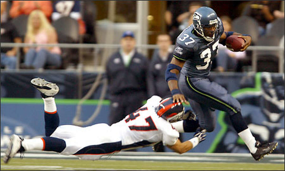 Seahawks running back Shaun Alexander makes a 7-yard gain against the Broncos' John Lynch during the first quarter.