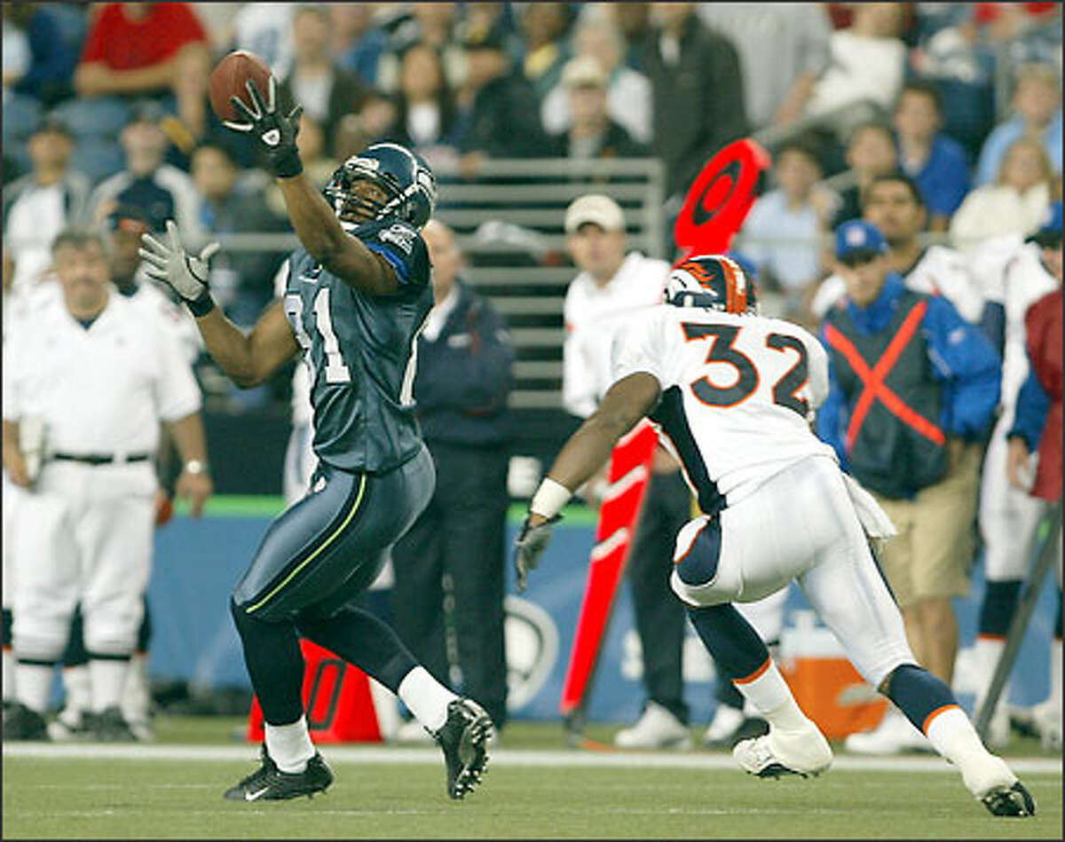 Seahawks wide receiver Koren Robinson hauls in a 10-yard pass from Seneca Wallace right in front of Broncos safety Chris Young during the third quarter.