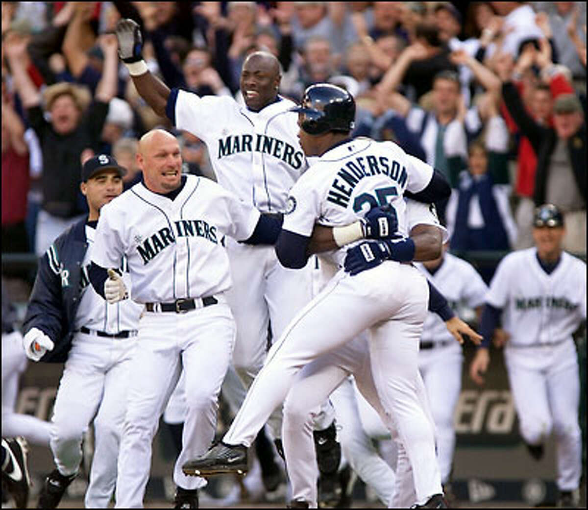 Jay Buhner, left, and Mike Cameron lead the charge out of the dugout to greet Rickey Henderson after he scored Seattle's winning run on a ninth-inning bunt by Carlos Guillen.