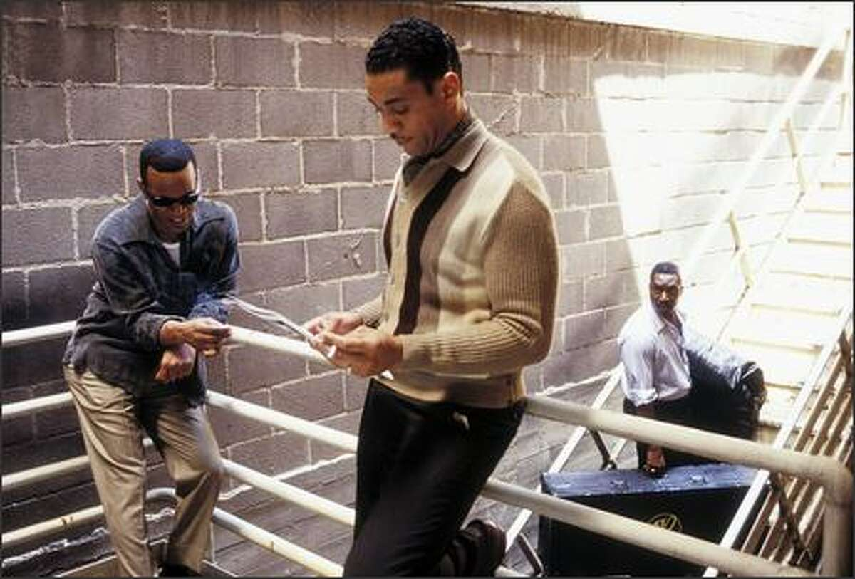Ray Charles (Jamie Foxx, left) believes his early manager, Jeff Brown (Clifton Powell, right) is cheating him and replaces him with Joe Adams (Harry Lennix, center).