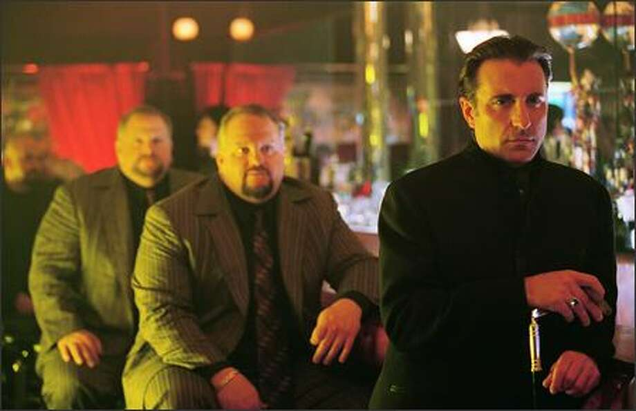 Ruthless entrepreneur Terry Benedict (Andy Garcia) would love nothing more than exacting revenge on the brash crew who robbed $160 million from his casinos –- especially their ringleader, Danny Ocean (George Clooney), who stole Benedict's girlfriend in the process. The power twins David and Larry Sontag are in the background. Photo: Warner Brothers