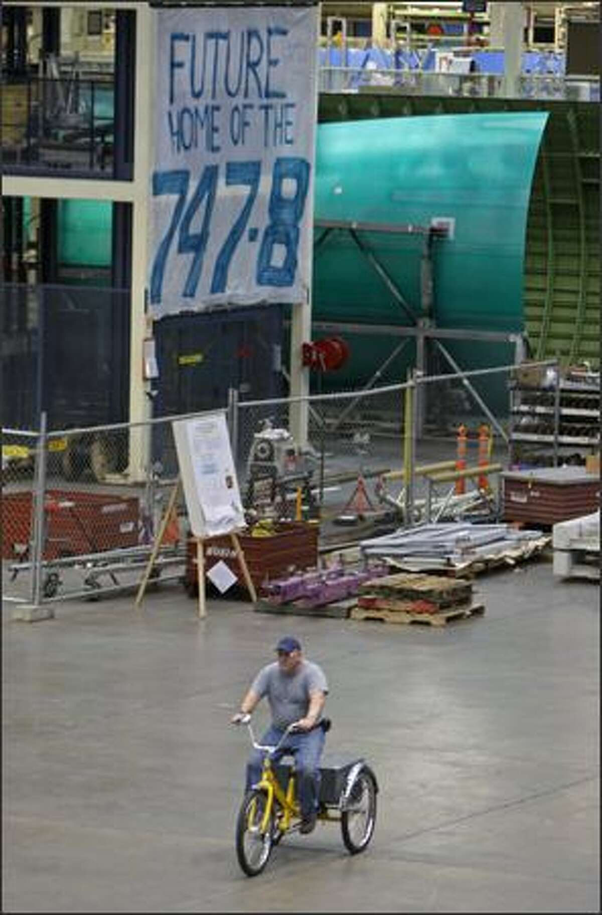 A Boeing employee rides a tricyle on the floor of a production line hangar at the Boeing factory.