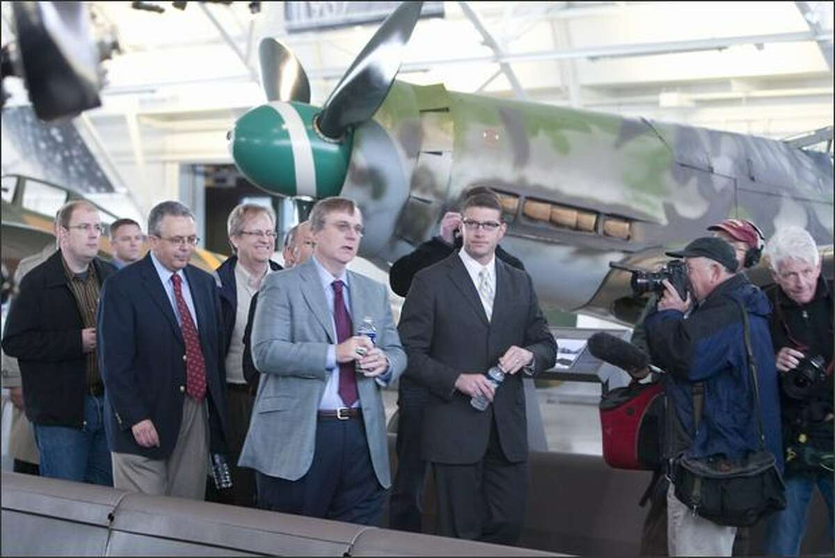 Paul Allen, center, glasses, gray jacket, leads a group of VIPs, members of the press and politicians through a tour of his warplanes after opening ceremonies to open Paul G. Allen's Flying Heritage Collection in a hanger at the south end of Paine Field, Everett, WA. Just behind him on left is Adrian Hunt, Executive Director of the Flying Heritage Collection, and on the right of Allen is Aaron Reardon, Snohomish County Executive.