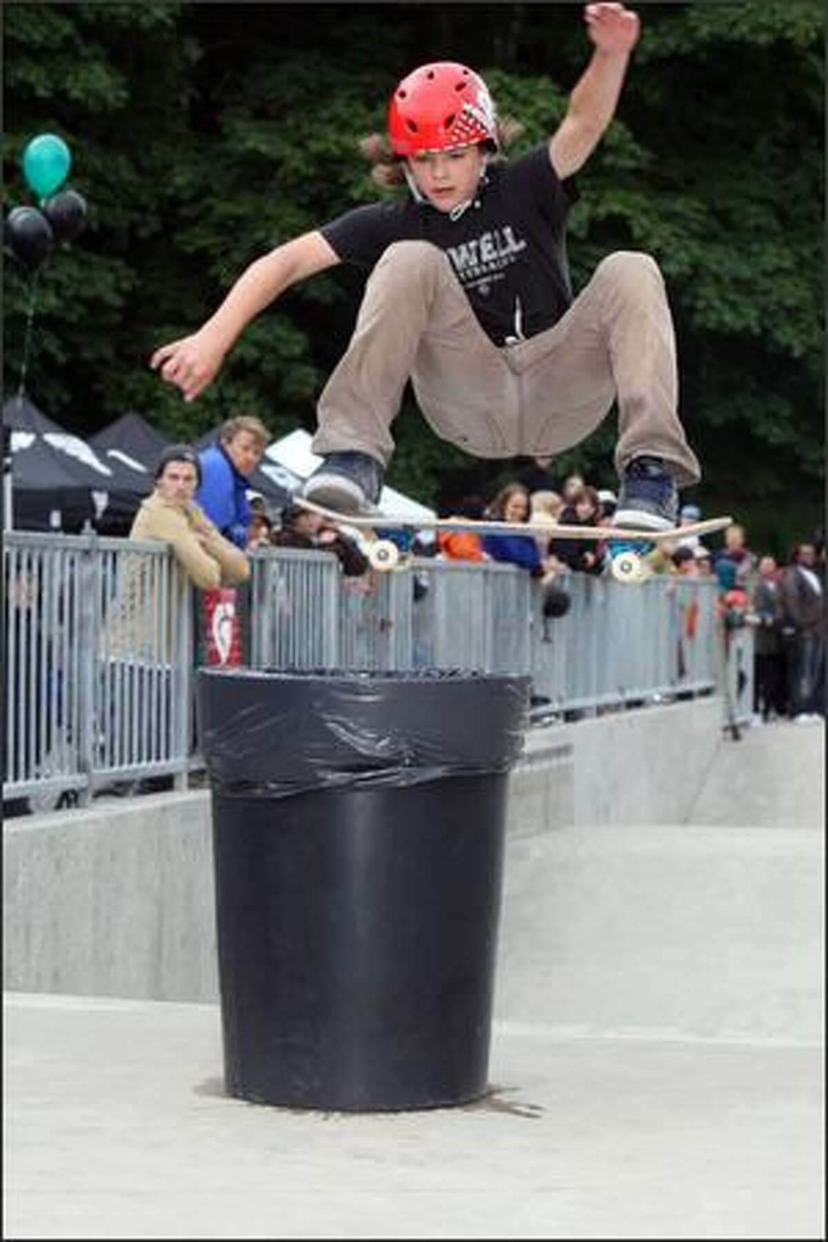 Brogan Robinson, 14, from Portland, leaps over a garbage can during a skateboard contest.