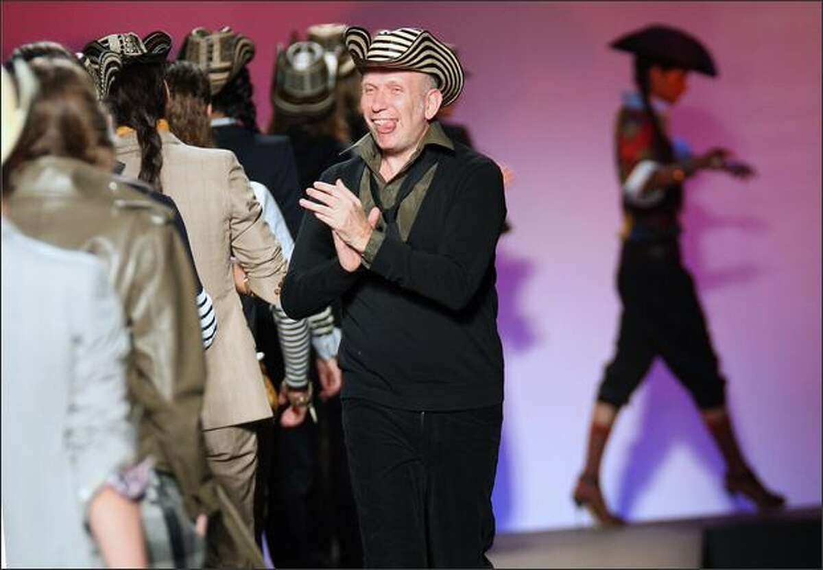 French designer Jean-Paul Gaultier applauds models at the end of the presentation of his collection.