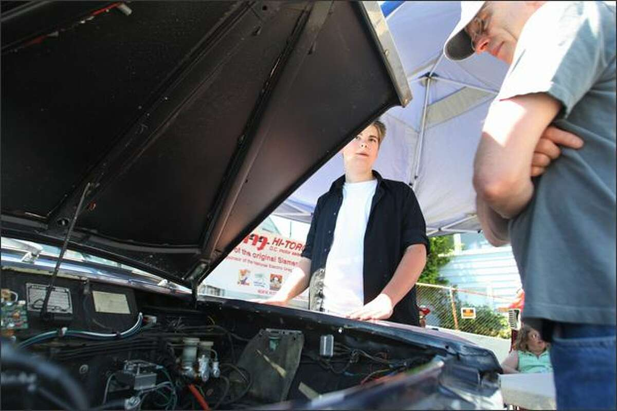 Michael Henry (left), 17, from Vancouver, Wash., talks about his electric 1970 Datsun 1600 pickup truck with Rob Westcott from Bellvue on Saturday at the Greenwood Car Show. Henry bought the car with his father, Damon Henry, for $500 in 2007 and they converted it to electric. Michael uses the car to drive to school. The Greenwood event is the