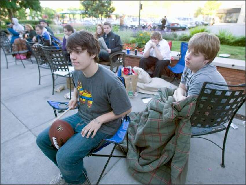 Taylor Jacobs, left, beats on a football with a drumstick as he and Travis Lumus wait in line to purchase an iPhone 3G at the University Apple Store on Friday In Seattle. The two Seattle residents were first in line and had been waiting since 5:30 pm Thursday.
