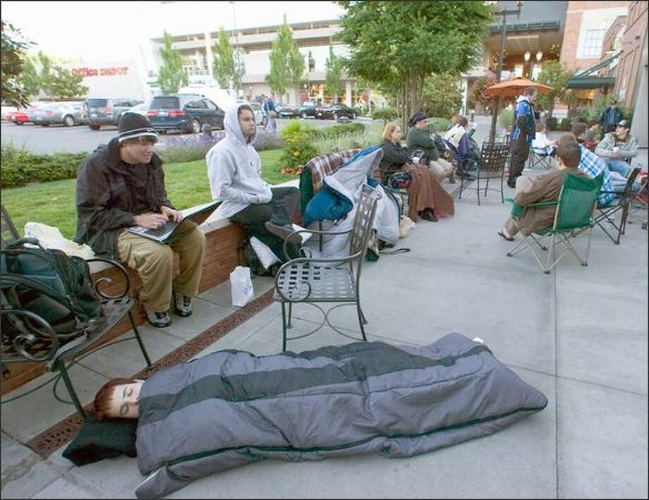 Eager geeks camped out for the new iPhone. Here, Ludley Neto takes a nap in a sleeping bag while Brenner Melo e-mails while waiting in line to purchase an iPhone 3G at the Apple Store in Seattle's  University Village. The two University of Washington students had been waiting since midnight. Photo: Jim Bryant, Seattle Post-Intelligencer
