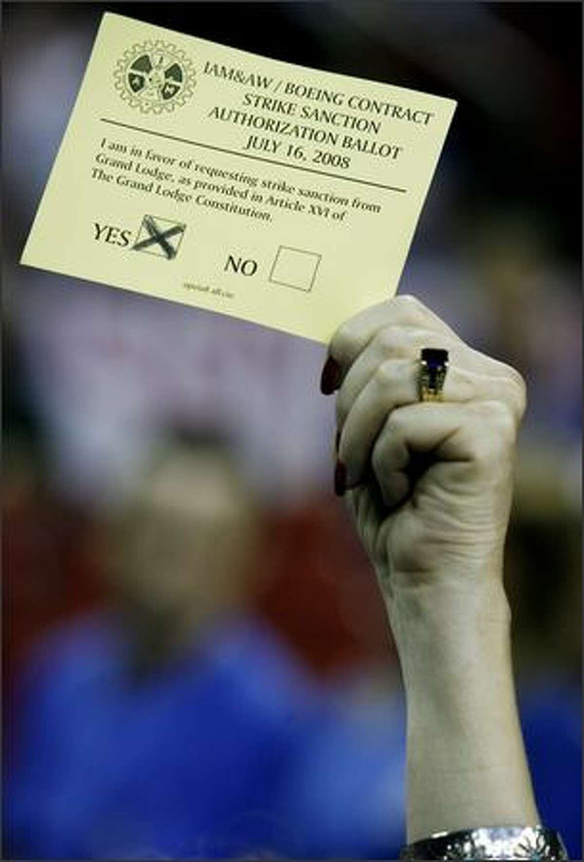 A Boeing machinist holds aloft a strike authorization ballot in Key Arena.