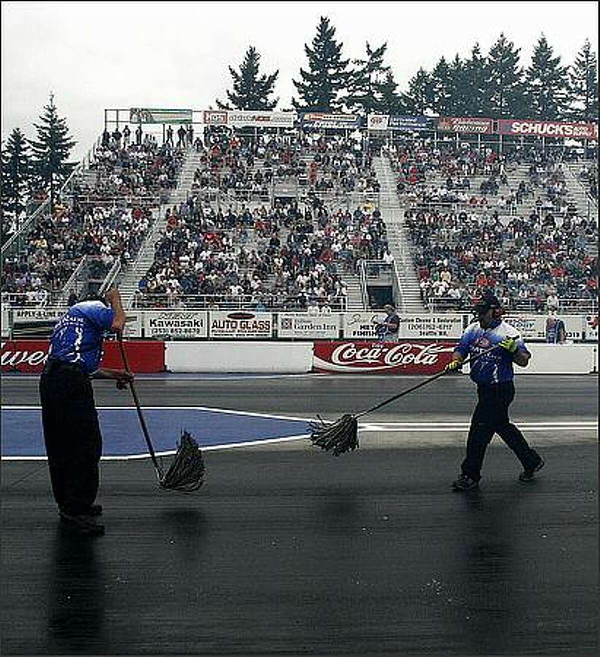 Workers use mops to clean off the raceway at the NHRA finals at Pacific Raceway in Kent Friday evening.