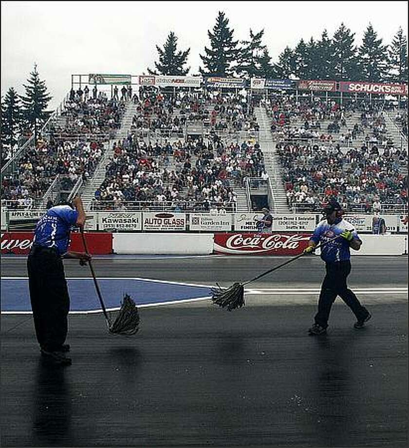 Workers use mops to clean off the raceway at the NHRA finals at Pacific Raceway in Kent Friday evening. Photo: Kristine Paulsen, Seattle Post-Intelligencer