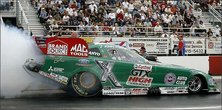 John Force races his Castrol GTX High-Mileage Ford Mustang funny car Friday during the first round of the NHRA Nationals at Pacific Raceway in Kent.