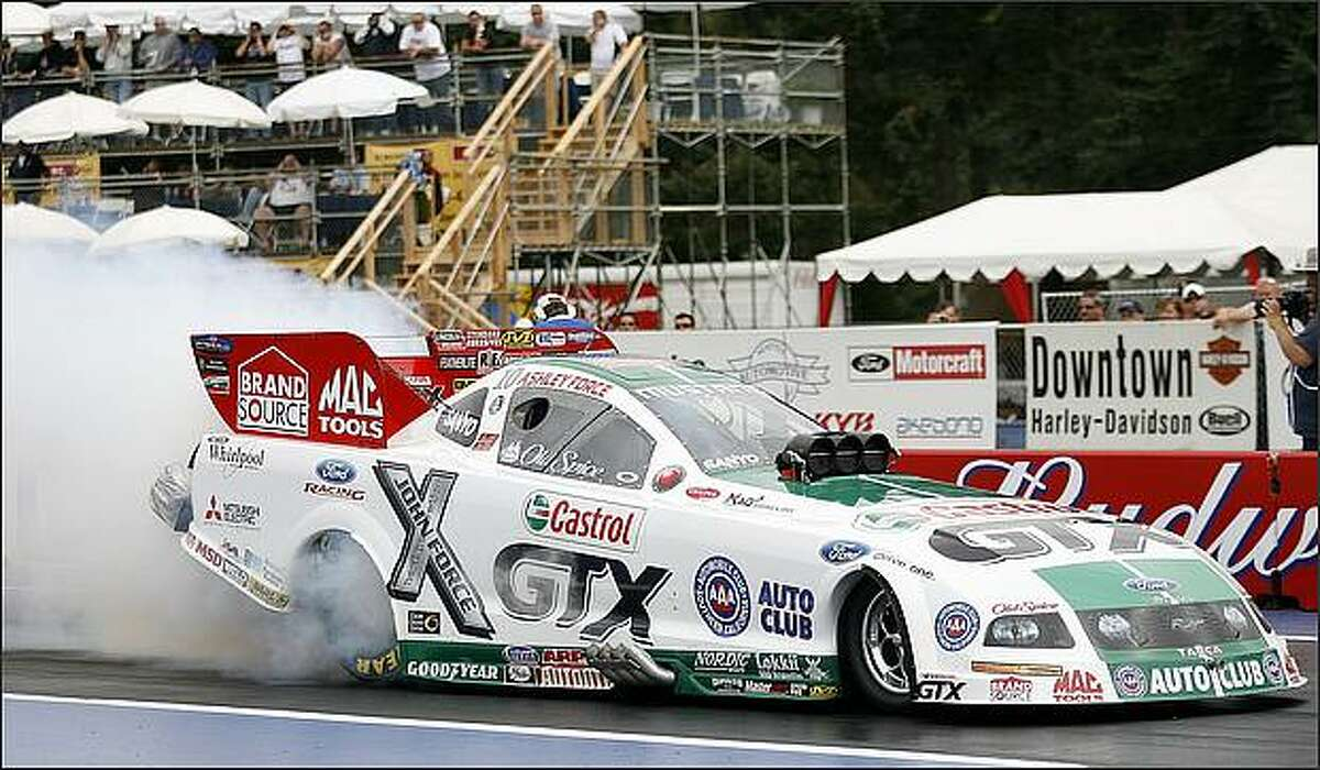 Ashley Force races her Castrol GTX Ford Mustang funny car Friday during the first round of the NHRA Nationals at Pacific Raceway in Kent.
