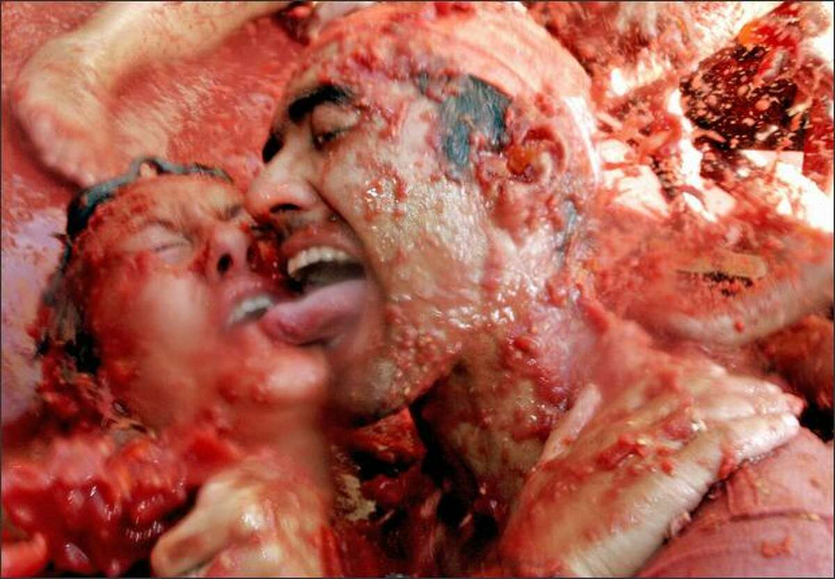 A couple covered in tomato juice are pictured during the