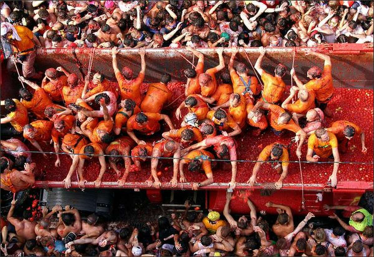Participants throw tomatoes from a truck during the
