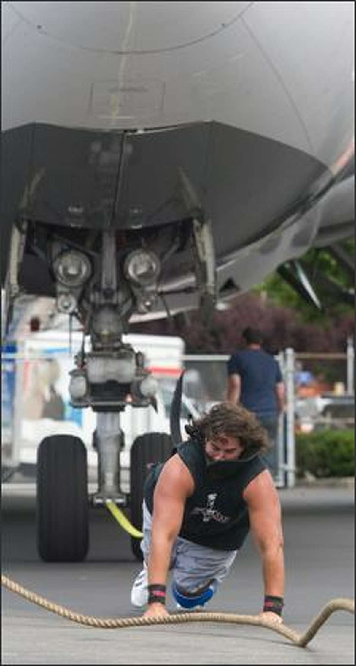 Tacoma strongman Mark Kirsch falls as his harness breaks while pulling a 200,000-pound Boeing 767 cargo jet at the Big Brothers Big Sisters Big Plane Pull at Boeing Field. Kirsch did pull the jet between 20 and 30 feet using a replacement harness.