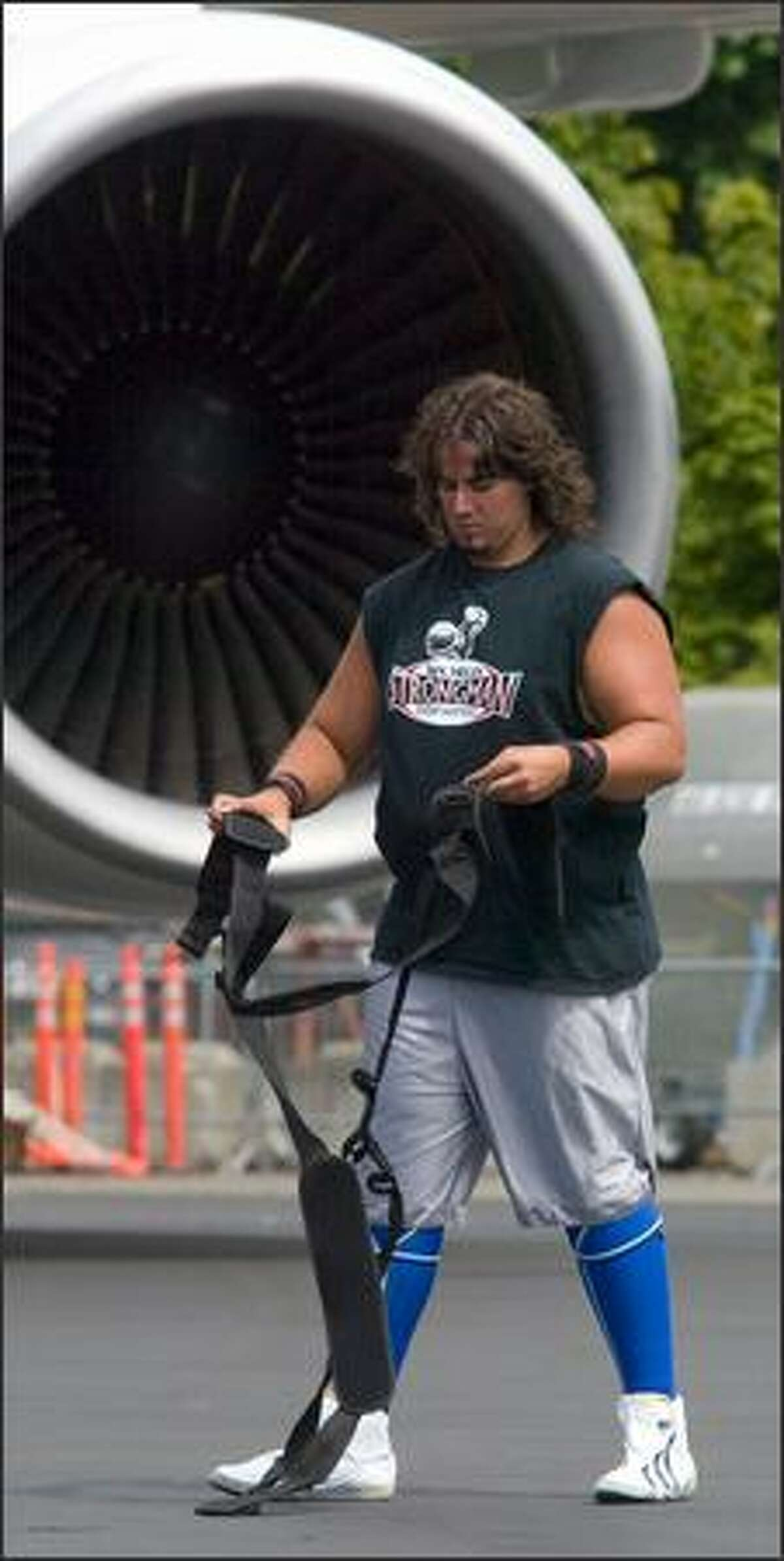 Tacoma strongman Mark Kirsch inspects a harness that broke while pulling a Boeing 767 cargo jet at the Big Brothers Big Sisters Big Plane Pull at Boeing Field.