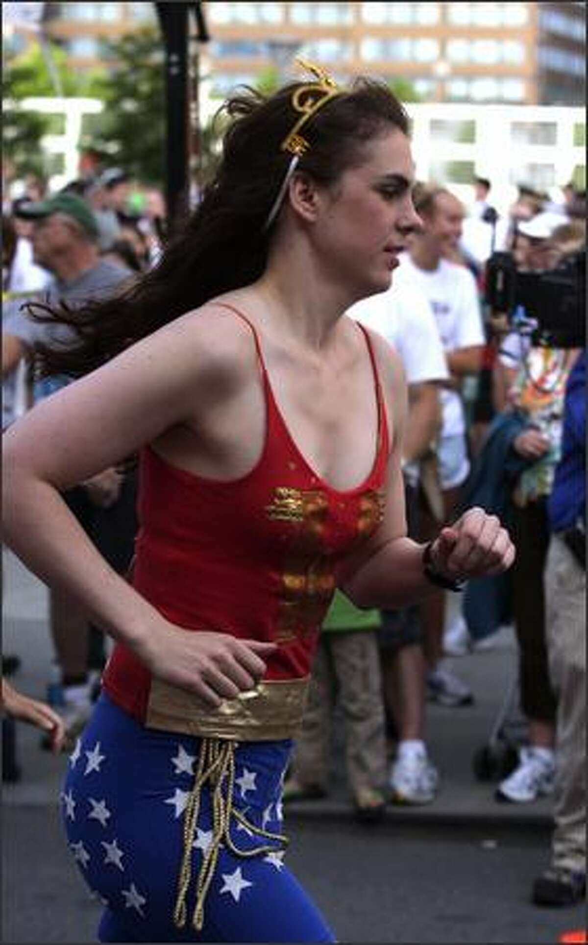 A participant dressed as Wonder Woman starts the 8K Torchlight Run at Seafair.