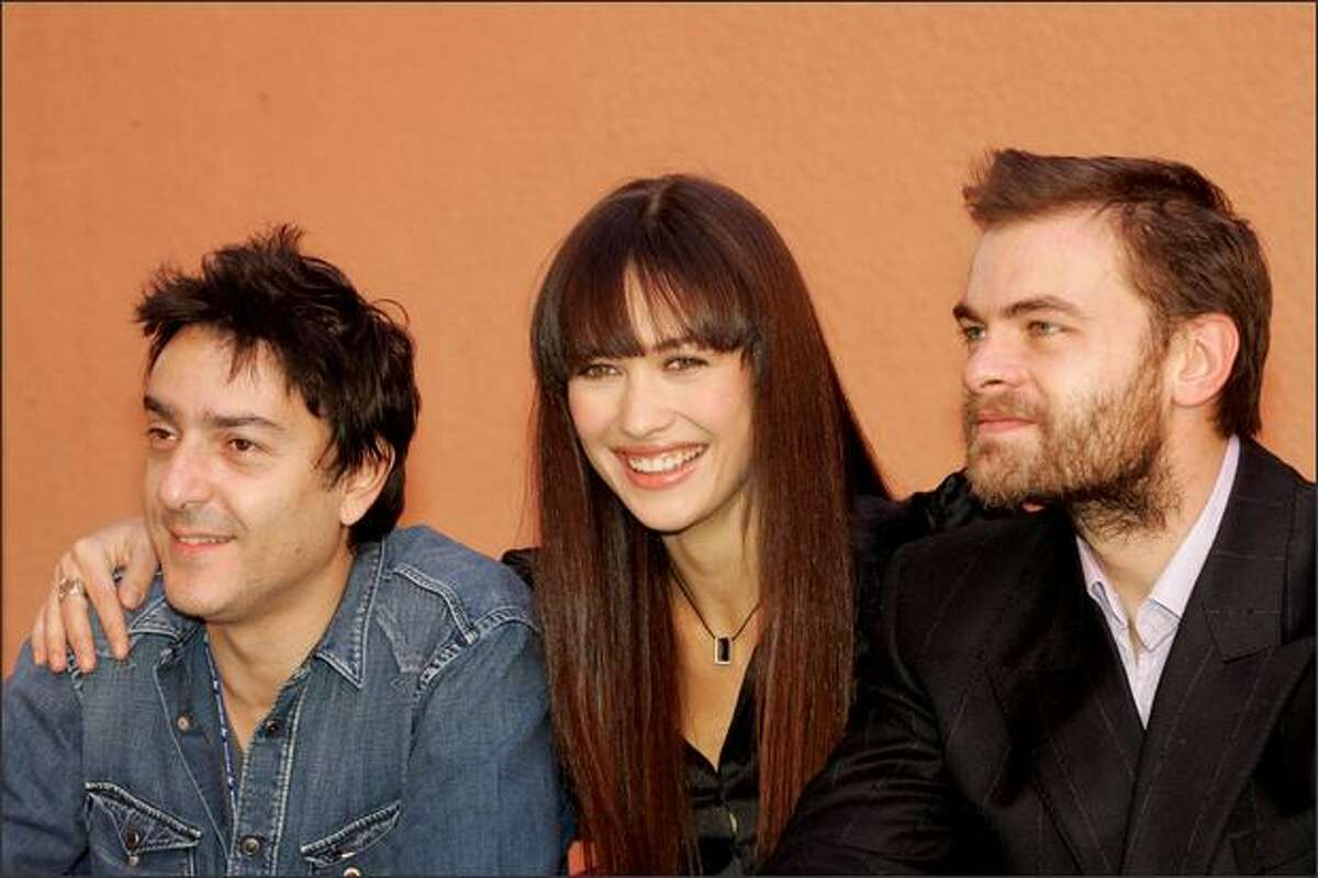 French actor Clovis Cornillac, Olga Kurylenko (C) and Yvan Attal (L) pose during the photocall of the film