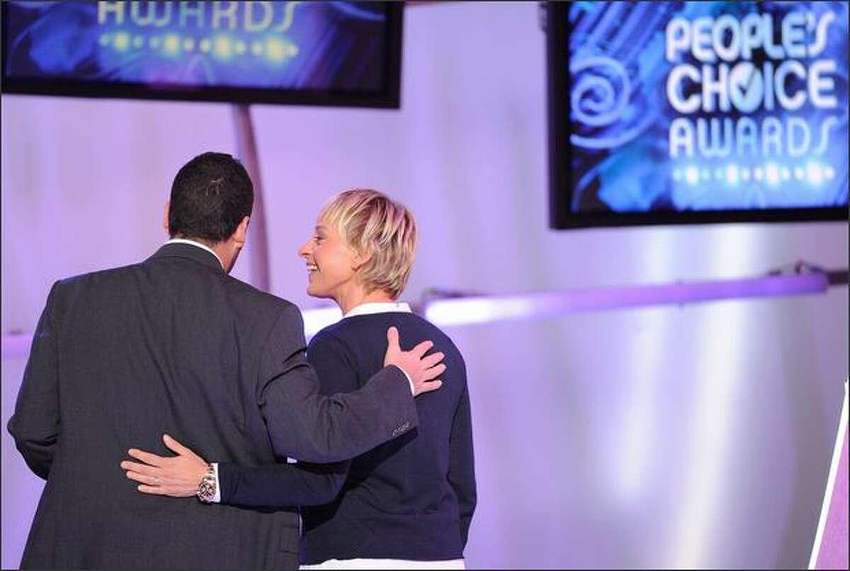 Presenter Ellen DeGeneres (right) and actor Adam Sandler, winner of the Funny Male Star award, walk off stage.