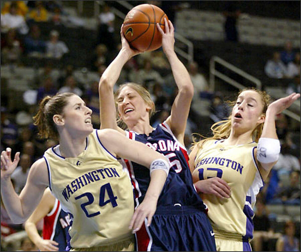 Arizona's Krista Warren, center, grabs a rebound between Washington's Kellie Dalan, left, and Guiliana Mendiola, right, in the first half of the semifinals of the Pacific 10 Conference Championships in San Jose, Calif., Sunday, March 9, 2003.