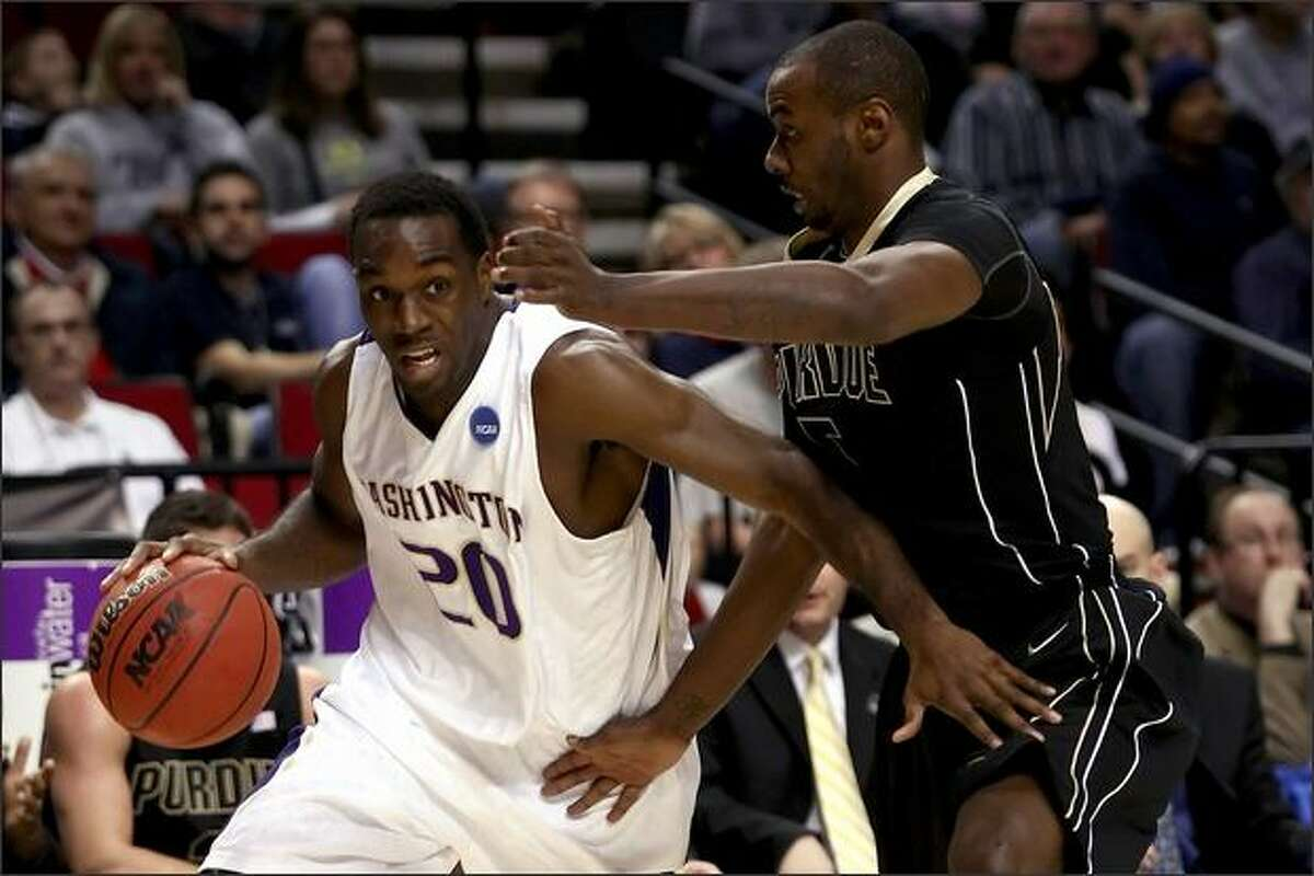 Quincy Pondexter of the Huskies drives on Keaton Grant of Purdue in the first half.