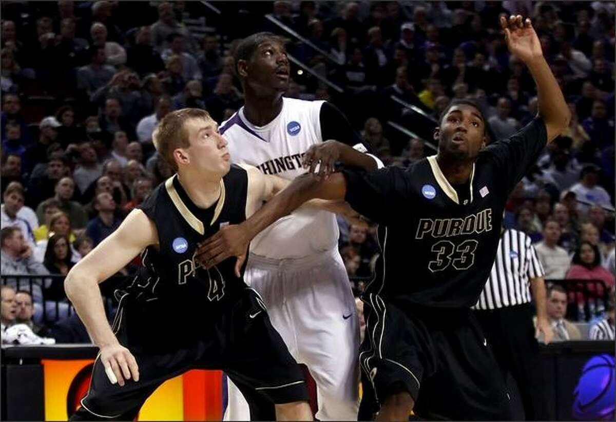 Darnell Gant of the Huskies is boxed out by Robbie Hummel (4) and E'Twaun Moore of Purdue in the first half.