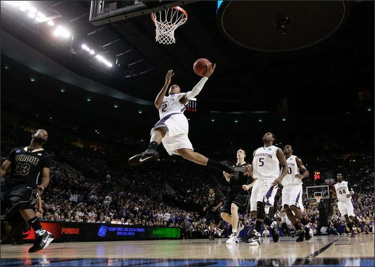 Isaiah Thomas of the Huskies goes up for a shot in the first half.