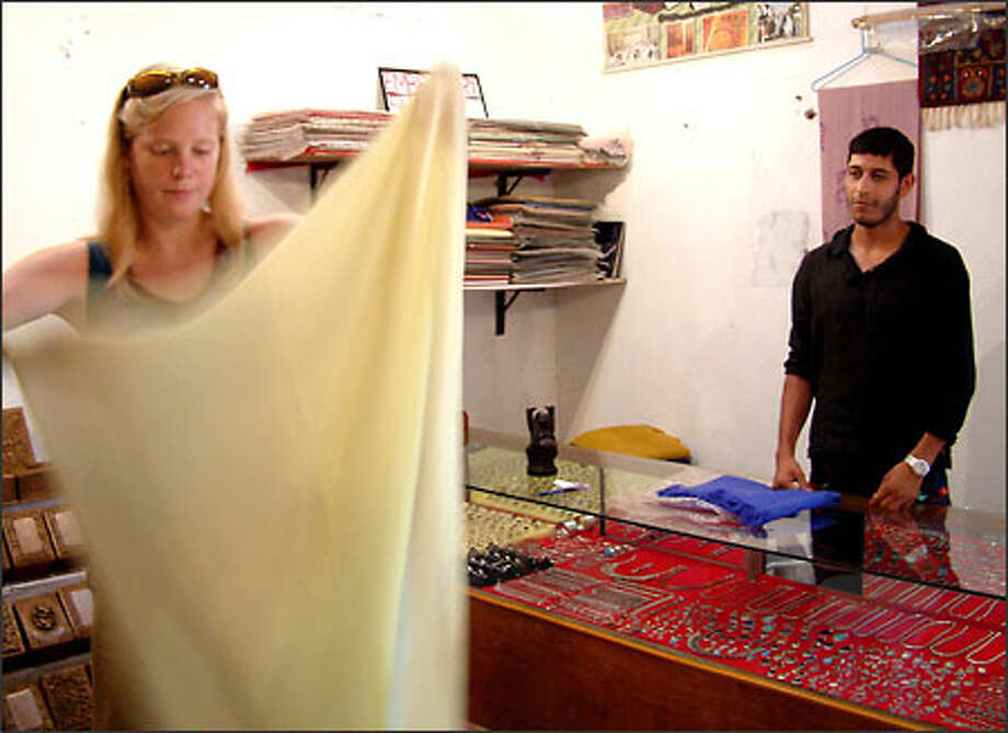 Tariq Ahmed Wani watches as Katrin Lepik of Seattle decides how much money to offer him for one of his pashmina shawls. A native of Kashmir, he sells pashmina items to tourists in the Indian state of Goa. Photo: Winda Benedetti, Special To Seattle Post-Intelligencer