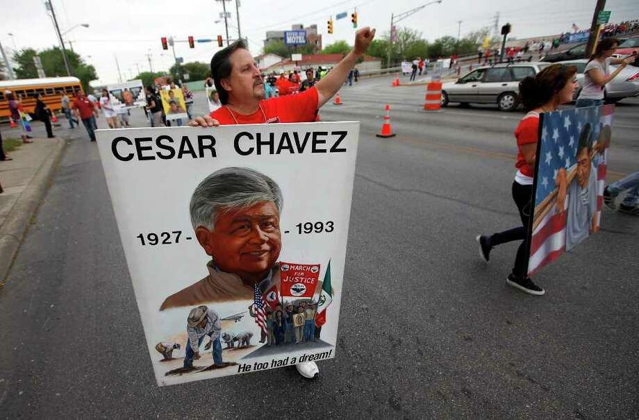 Artist Abel Ortiz gestures as he carries one of his paintings depicting labor and civil rights leader Cesar Chavez during the 15th annual Cesar Chavez March for Justice on Saturday, Mar. 26, 2011. Kin Man Hui/kmhui@express-news.net Photo: KIN MAN HUI, Kin Man Hui/kmhui@express-news.net / San Antonio Express-News NFS