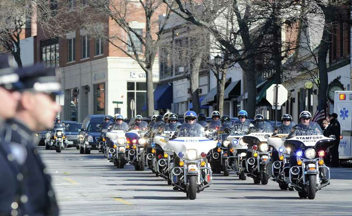 Area motorcycle police lead the funeral procession for Greenwich Police Officer James Genovese on Greenwich Avenue near St. Mary Church, Saturday, March 26, 2011.