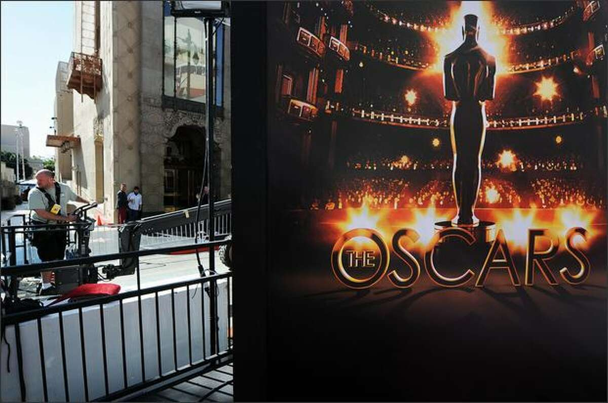 A workman steers a vehicle passing a Oscars poster as preparation continues for the 81st Academy Awards.