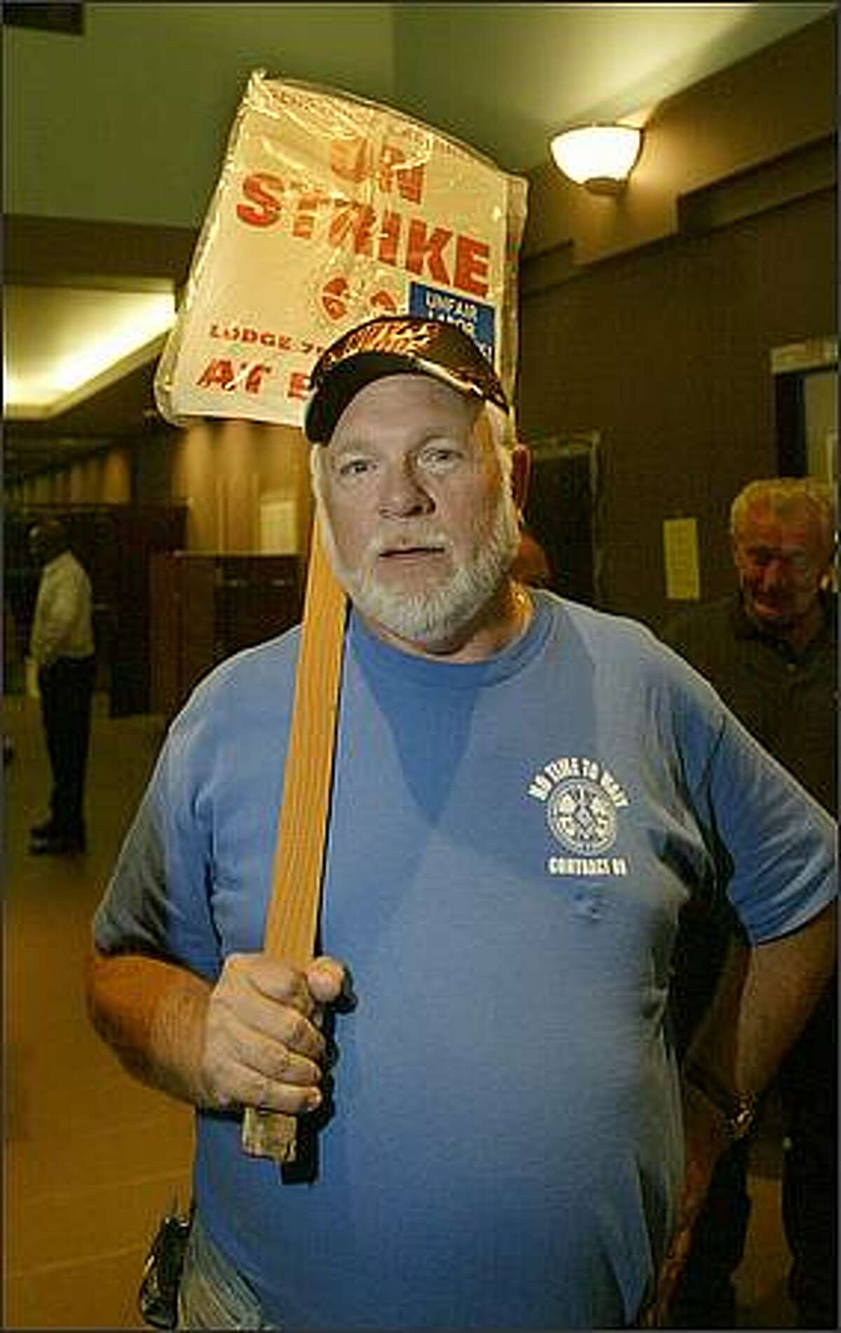 Rick Herrmann who has worked for Boeing for 41 years holds a strike sign inside Seattle Union Hall.