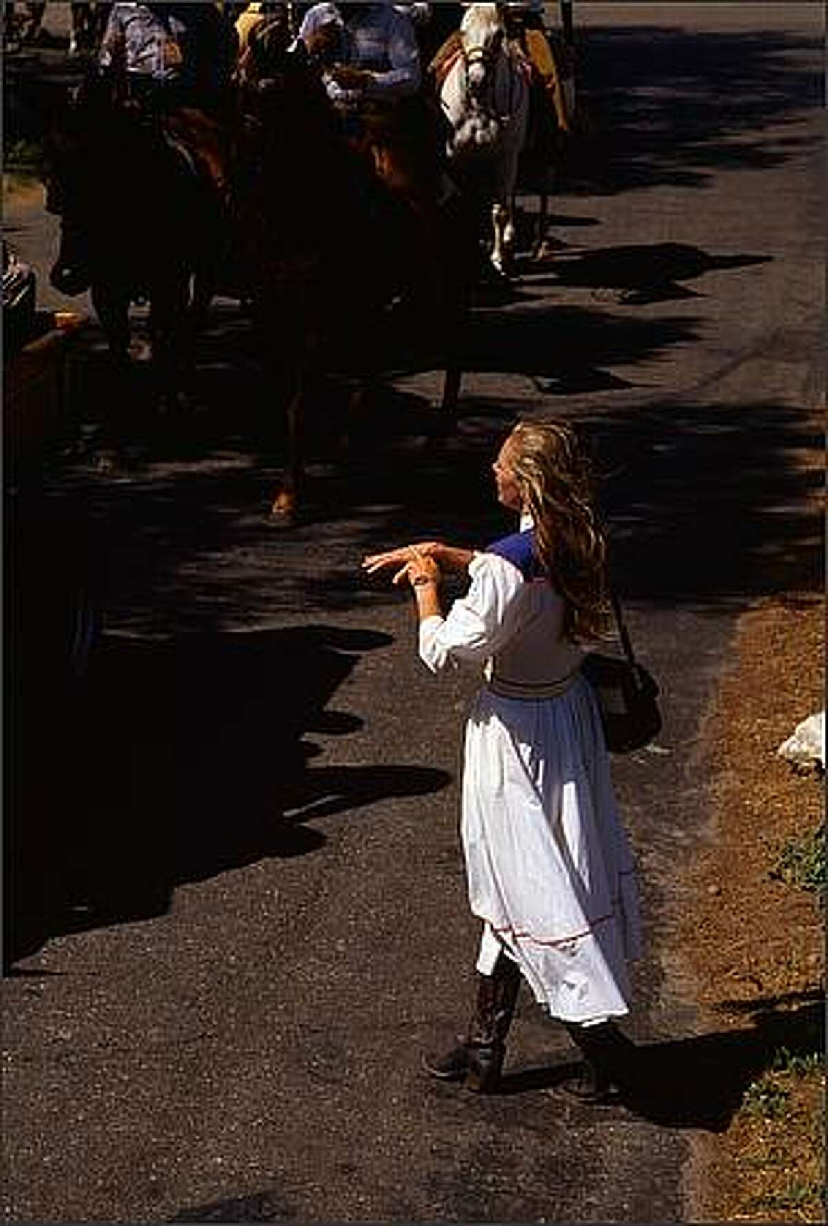 May 7, 1988, Solvang, California: As the mounted Rancheros enter the grounds of the Mission Santa Ines for the annual Blessing of the Horses, an unidentified woman calls out to them and with her middle finger extended rubs it on the back of her other hand in a circular motion. Photo by: Tomas / Polaris