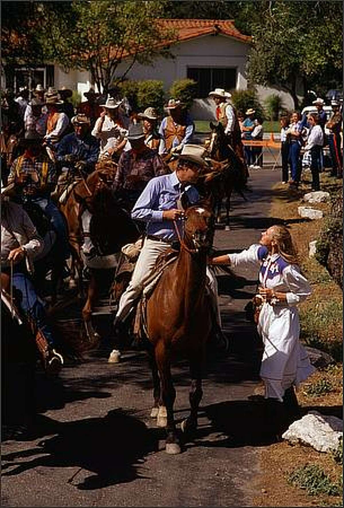 May 7, 1988, Solvang, California: Wealthy San Francisco securities executive and Ranchero guest Claxton Long is approached by an unidentified woman as he enters the Santa Ines Mission Grounds on his way to the Ranchero send-off ceremonies. Later in the week, during the ride, Long died as a result of a bar brawl with a local welder. Local newspapers have reported that there is a growing resentment for the annual gathering of wealthy and powerful men. Photo by: Tomas / Polaris