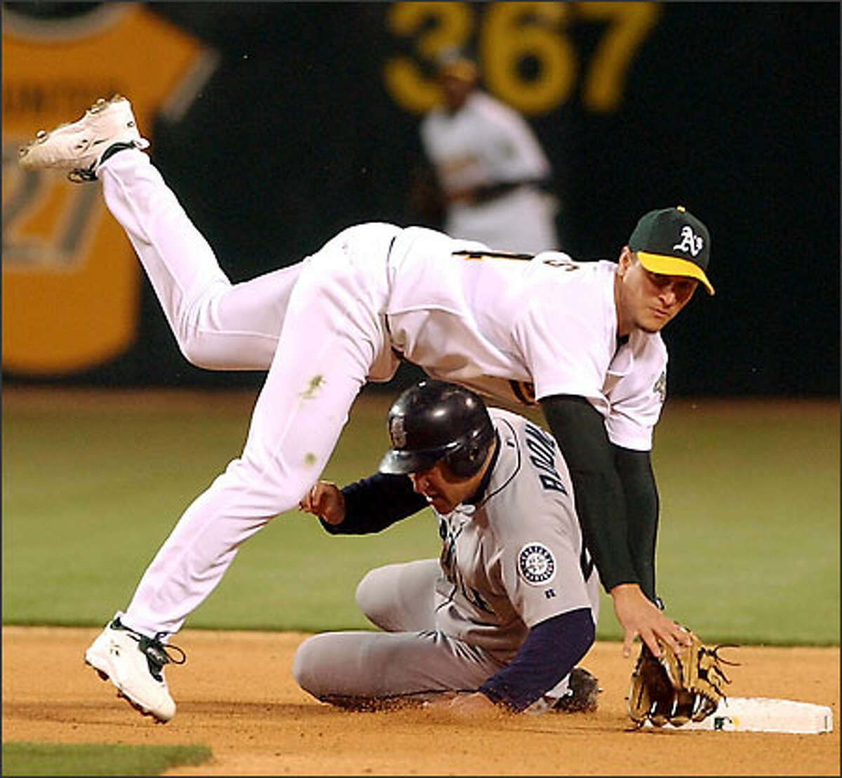 Oakland second baseman Mark Ellis falls over Boone, his Mariners counterpart, completing a double play that ended the fourth inning.