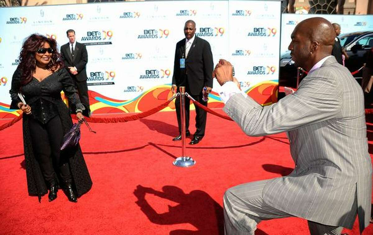 Former NBA player John Salley (R) takes a photo of singer Chaka Chan during arrivals at the 2009 BET Awards held at the Shrine Auditorium on Sunday in Los Angeles, California.