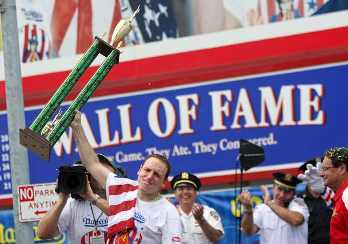 Joey Chestnut (left) holds up his trophy after defeating Takeru Kobayashi (not seen) 68-64 in the Nathan's Famous Fourth of July hot dog eating contest in Coney Island in the Brooklyn borough of New York on Saturday, July 4, 2009. Chestnut was the defending champion.