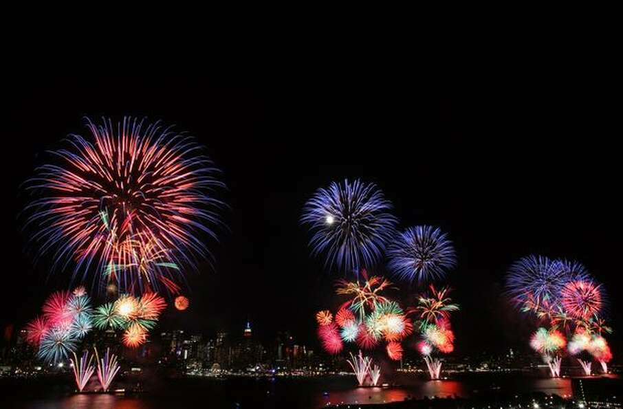 The New York skyline is seen in the distance as fireworks explode over the Hudson River.