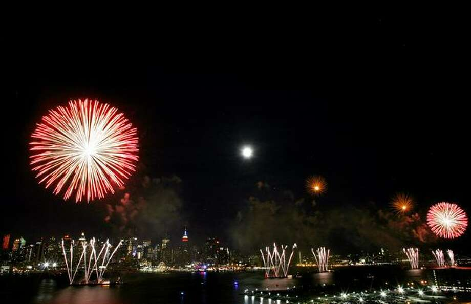 The New York skyline is seen in the distance as fireworks explode over the Hudson River. Photo: Getty Images