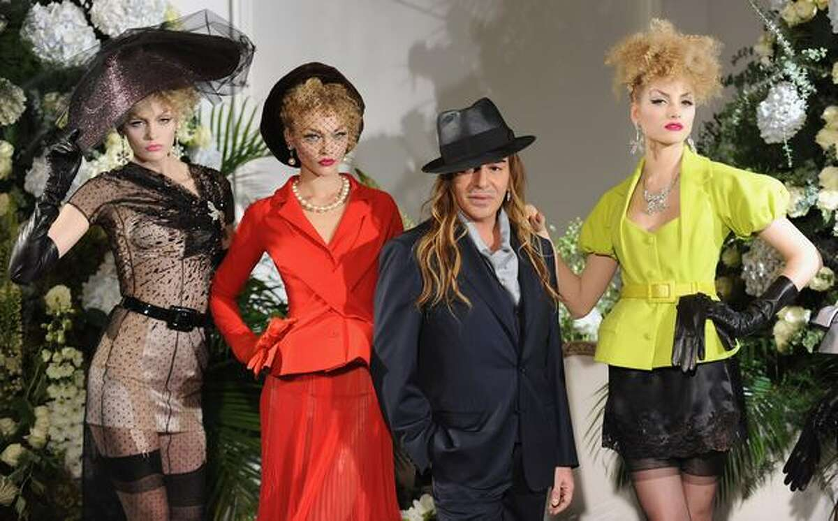 Fashion Designer John Galliano poses with models during the Christian Dior Haute Couture fashion show on Monday in Paris, France.