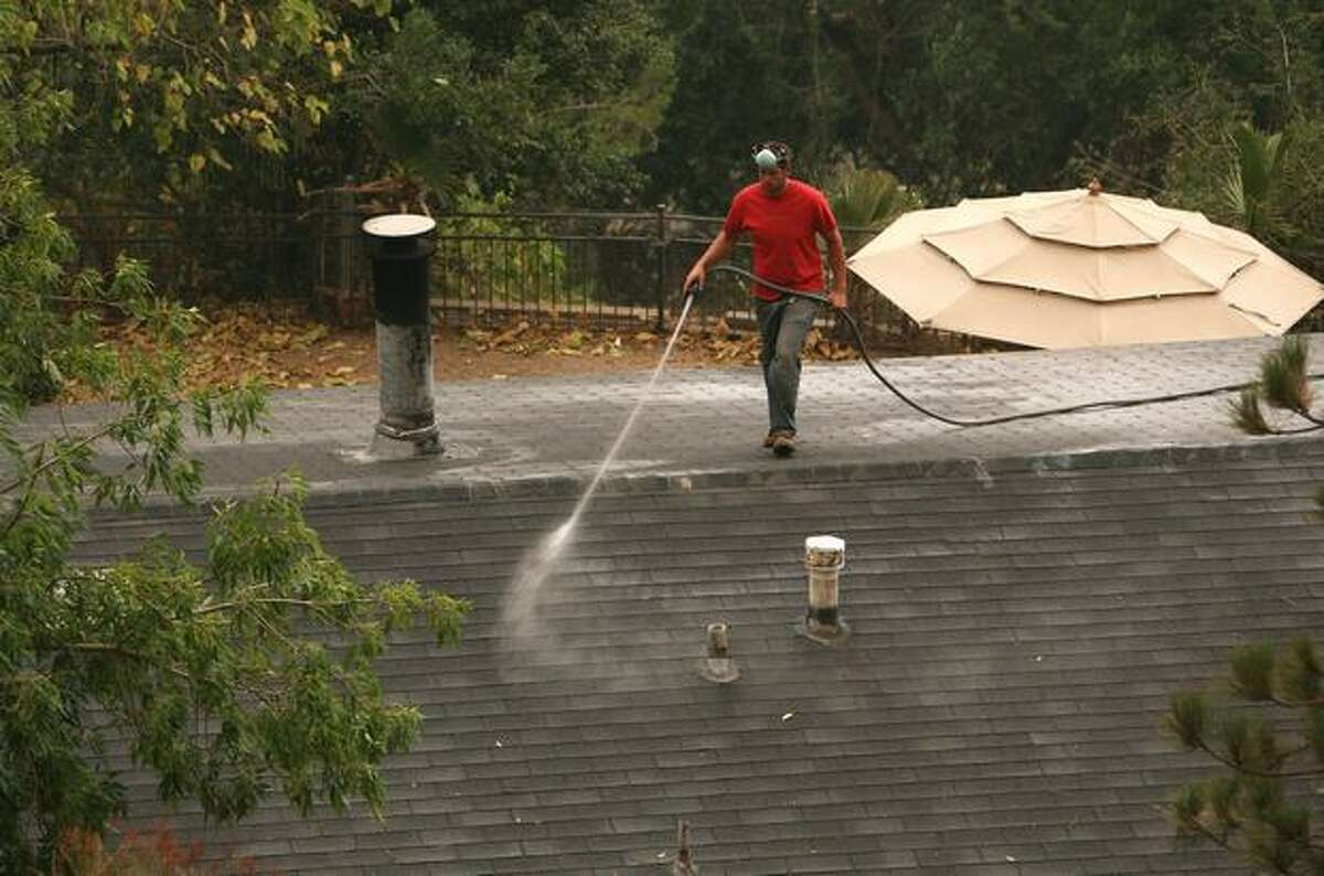 A resident sprays water on his roof as a back fire nears the rear of his home Tuesdayin Tujunga, Calif. The out-of-control Station Fire has burned more than 120,000 acres and 50 homes, and has forced thousands of evacuations as nearly 10,000 homes are threatened.