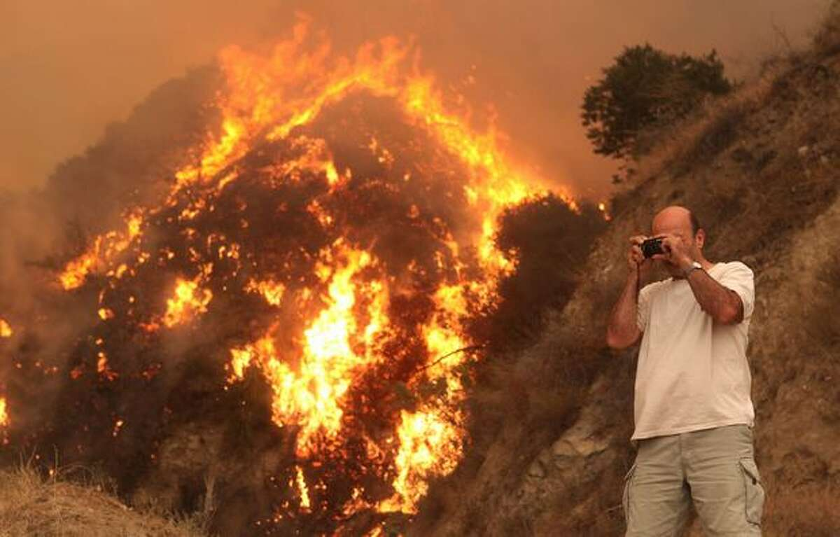 A resident takes a photograph of a back fire that burns near his home in Tujunga, Calif.