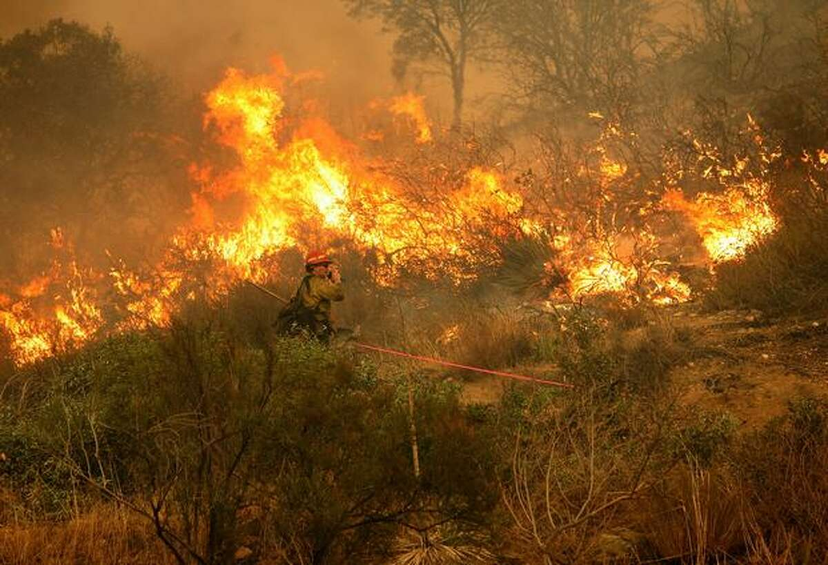 A Los Angeles City firefighter monitors a backfire in Tujunga, Calif.