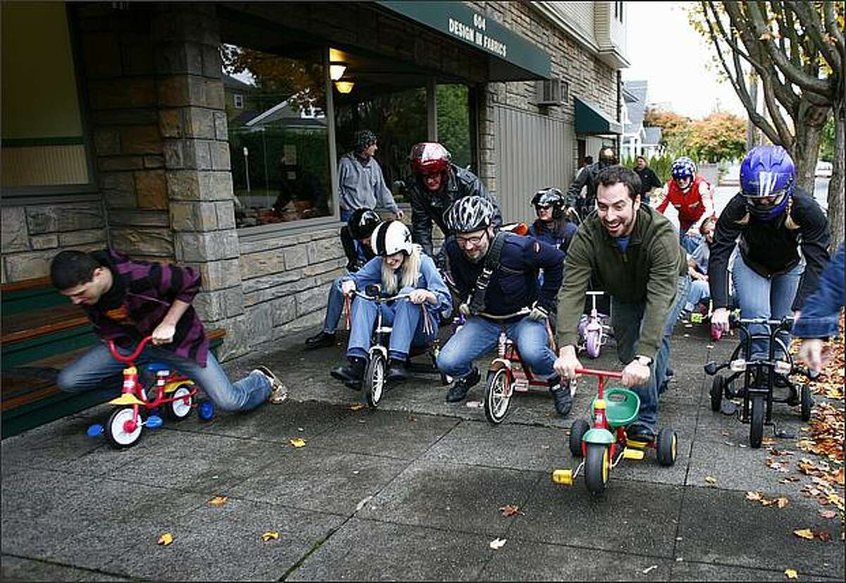 Three wheeled competitors take off as the Queen Anne Tricycle Race begins on Sunday in Seattle. The competition began on the top of the hill at Targy's Tavern and ended after all the riders made it safely to the bottom. Helmets and safety gear were encouraged for participants who screamed down some of Queen Anne's steep hills. Many of the participants, either because of their kiddie tricycles falling apart, or because of fear of the steep hills, carried their wheels for parts of the race.