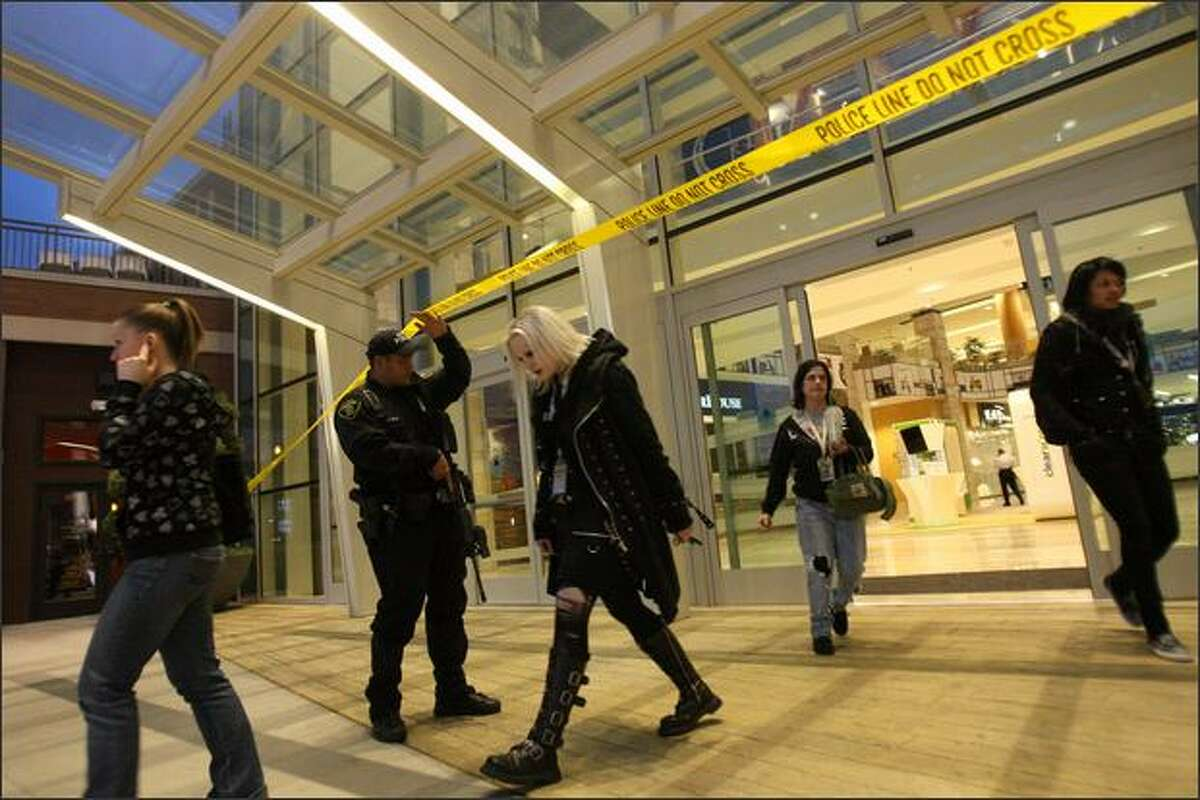 A Renton Police Officer lifts police tape to allow people to exit Southcenter mall after a shooting, in which two people were shot and were being treated for wounds at Harborview Medical Center. One later died.